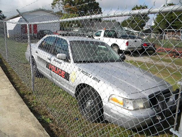 "The city of Calhoun's three police cars were inside the fence Wednesday at the city lot next door to city hall. The town's three police officers were ""indefinitely'' let go on Monday."