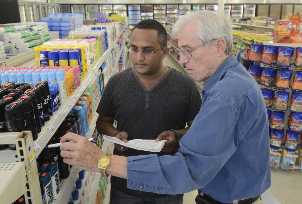 Store owner and manager Moe Saleh, left, and Dennis Westmeier, treasurer of the Westside Community Association, check item placement  Thursday at One Stop Shop, a newly opened grocery store near College Hill Courts.