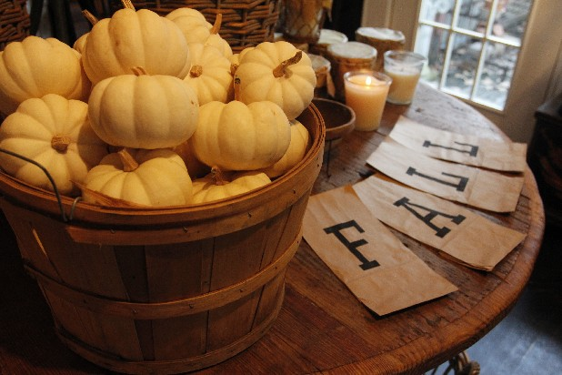 Small white pumpkins in a basket can create a focal point, while simple block letters printed on brown paper bags are an easy way to send a message.