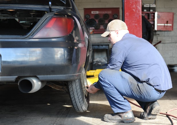 Dusty McNabb repairs a flat tire at National Tire and Battery on Rossville Boulevard on Sunday. The auto-repair shop received multiple cars with flat tires after motorists drove on Dodds Avenue Saturday night or Sunday.