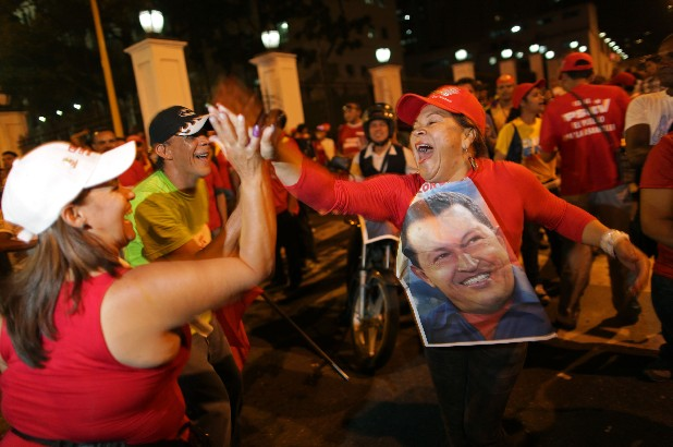 Supporters of Venezuela's President Hugo Chavez cheer after polling stations closed and before any results were made available in Caracas, Venezuela, Sunday, Oct. 7, 2012. Venezuela's electoral council says Chavez has won re-election, defeating challenger Henrique Capriles.