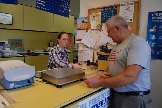 Jimmy Eakins, right, talks with postal clerk Jamie Curtis at the U.S. Post Office in Hollywood, Ala., Thursday. The post office is within sight of the Bellefonte Nuclear Plant. It is one of eight in Jackson County on a preliminary list for a reduction in operating hours. Eakins, who visits from work daily, says he'll have to adjust his work schedule if hours change.