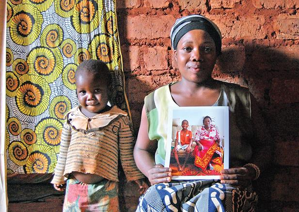 Jackie Niyonzima, 27, and her son Elias Vyizigiro, 5, pose with a picture of her oldest son and her mother who now live in Chattanooga. Money that Jackie's mother sent back to Burundi helped build this small mud house.