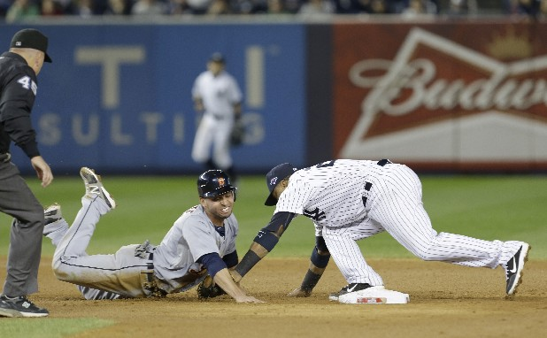 Detroit Tigers' Omar Infante dives back into second as New York Yankees' Robinson Cano reaches to tag him in the eighth inning of Game 2 of the American League championship series Sunday, Oct. 14, 2012, in New York. Infante was called safe on the play by umpire Jeff Nelson.