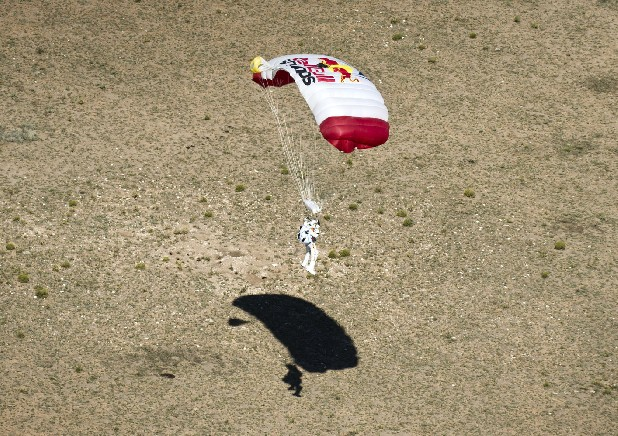 In this photo provided by Red Bull, pilot Felix Baumgartner of Austria lands in the desert after his successful jump on Sunday, Oct. 14, 2012 in Roswell, N.M. Baumgartner came down safely in the eastern New Mexico desert minutes about nine minutes after jumping from his capsule 128,097 feet, or roughly 24 miles, above Earth.