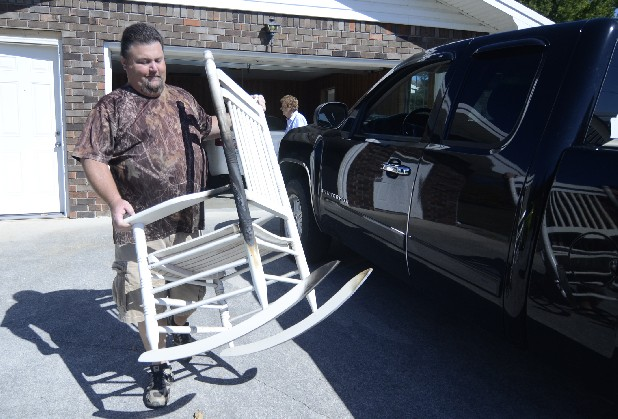 Stacey Banther carries a fire-damaged rocking chair out of his grandmother, Hazel Banther's, home. Banther's home was firebombed twice.