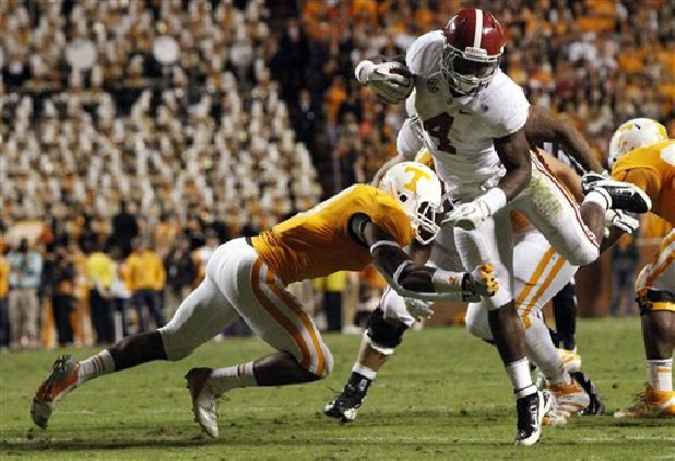 Alabama running back T.J. Yeldon (4) avoids a tackle by Tennessee defensive back Byron Moore (3) during the second quarter of an NCAA college football game on Saturday, Oct. 20, 2012, in Knoxville.