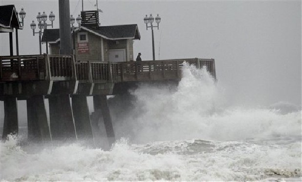 Large waves generated by Hurricane Sandy crash into Jeanette's Pier in Nags Head, N.C., Saturday, Oct. 27, 2012 as the storm moves up the east coast. Hurricane Sandy, upgraded again Saturday just hours after forecasters said it had weakened to a tropical storm, was barreling north from the Caribbean and was expected to make landfall early Tuesday near the Delaware coast, then hit two winter weather systems as it moves inland, creating a hybrid monster storm.
