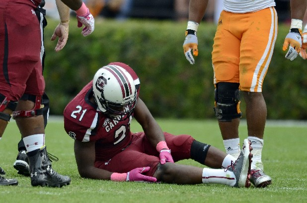 South Carolina running back Marcus Lattimore grabs his right knee after getting hit by Tennessee's Eric Gordon.