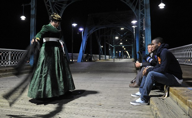 Hope Holloway tells the ghost story of the Walnut Street Bridge to guests J.J. Johnson, Adia Barnes, Chris Menerick and Amy Menerick, from right to left, during a Chattanooga Ghost Tour Tuesday night.