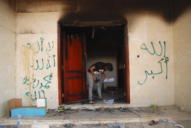 "A man looks at documents at the U.S. consulate in Benghazi, Libya, after an attack that killed four Americans, including Ambassador Chris Stevens. The graffiti reads, ""no God but God,""  ""God is great,"" and ""Muhammad is the Prophet."" CIA security officers went to the aid of State Department staff less than 25 minutes after they got the first call for help during the attack on the U.S. Consulate in Benghazi, Libya, U.S. intelligence officials said Thursday as they laid out a detailed timeline of the CIA's immediate response to the attack from its annex less than a mile from the diplomatic mission."