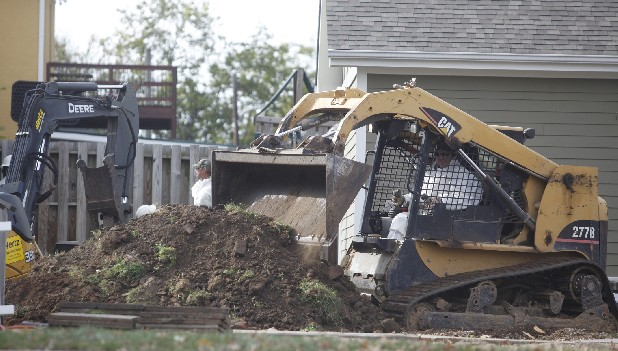 Workers move contaminated soil from the backyard of a home Tuesday morning. A crew from WRS Compass was back to work in Chattanooga on Tuesday to do more lead contamination clean up.