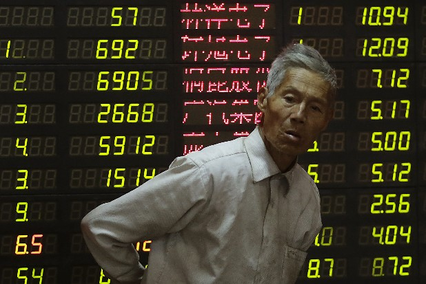 An investor looks at the stock price monitor at a private securities company in Shanghai, China. Asian stock markets tumbled Thursday after a ratings agency threatened to downgrade the U.S. if a solution to the so-called fiscal cliff isn't negotiated among lawmakers and newly re-elected President Barack Obama.