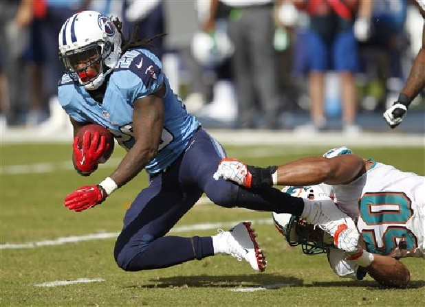 Tennessee Titans running back Chris Johnson is tackled by Miami Dolphins defensive end Olivier Vernon (50) during the first half of an NFL football game, Sunday, Nov. 11, 2012, in Miami.