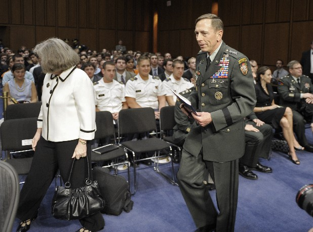 In this June 23, 2011, file photo, Gen. David Petraeus, center, walks with his wife Holly, left, past a seated Paula Broadwell, rear right, as he arrives to appear before the Senate Intelligence Committee during a hearing on his nomination to be Director of the Central Intelligence Agency on Capitol Hill in Washington. Petraeus quit Nov. 9, 2012, after acknowledging an extramarital relationship. As questions arise about the extramarital affair between Petraeus and his biographer, Paula Broadwell, she has remained quiet about details of their relationship. However, information has emerged about Jill Kelley, the woman who received the emails from Broadwell that led to the FBI's discovery of Petraeus' indiscretion. (AP Photo/Cliff Owen, File)