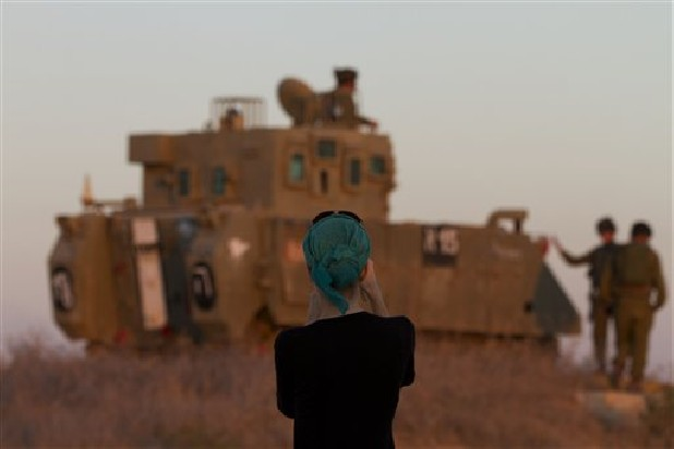 "A woman photographs Israeli soldiers on top an armored personal carrier close to the Israel Gaza Border, southern Israel,Thursday, Nov. 15, 2012. Israel's prime minister says the army is prepared for a ""significant widening"" of its operation in the Gaza Strip. Benjamin Netanyahu told reporters on Thursday that Israel has ""made it clear"" it won't tolerate continued rocket fire on its civilians."