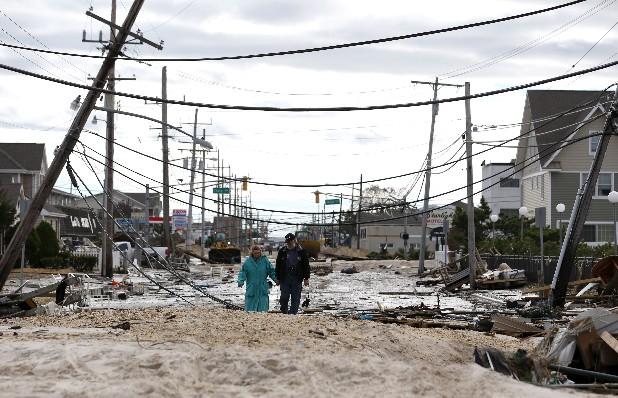 Robert Bryce, right, walks with his wife, Marcia Bryce, past downed utility poles and other debris from Superstorm Sandy on Route 35 in Seaside Heights, N.J. An Associated Press analysis of outage times from other big hurricanes and tropical storms suggests that, on the whole, the utility response to Sandy, especially in hardest-hit New York and New Jersey, was typical — or even a little faster than elsewhere after other huge storms.