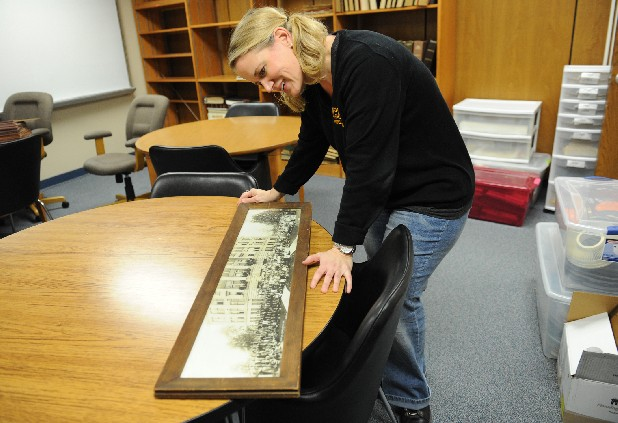 Central High School librarian Melinda Martin looks over a photograph of Central in the early 1900s Friday in the Central library. Martin is working to obtaining funding through grants to redo the school's library.