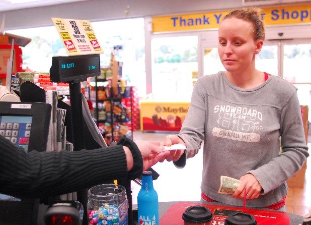 A customer buys a PowerBall lottery ticket at a gas station on Jenkins Road.