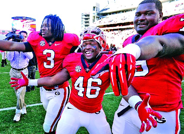 Georgia running back Todd Gurley (3), fullback Alexander Ogletree (46), and guard Mark Beard (79) celebrate their 42-10 win over Georgia Tech after an NCAA college football game, Saturday, Nov. 24, 2012, in Athens, Ga.