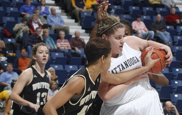 Ashlen Dewart of UTC holds onto a rebound as Wofford players attempt to wrestle it from her grasp during Thursday's game at McKenzie Arena.