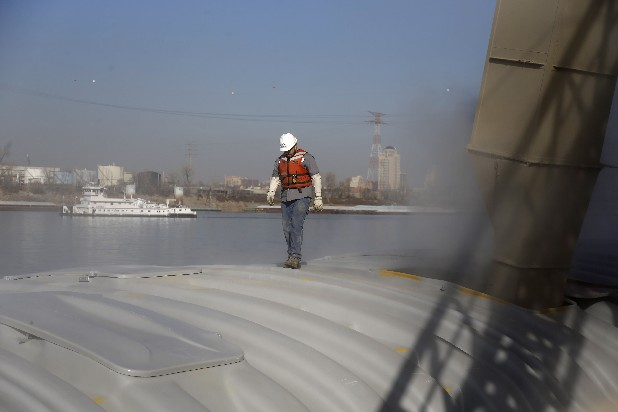 Dust floats in the air as Archer Daniels Midland employee Kenny Crowe walks on a barge while it is loaded with soybeans at an ADM river terminal along the Mississippi River Wednesday, Nov. 28, 2012, in Sauget, Ill. The potential closure of the river due to low water levels has raised concern for barge companies and others who use the river for shipping with a prolonged shutdown of the river possibly costing billions of dollars in losses.