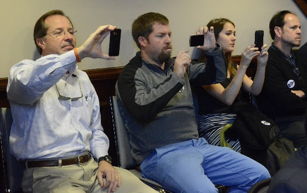 Jim Piersant, Ryan Piersant and Emily Piersant, from left, use their phones to record the Hamilton County Commission meeting while Joe Ledbetter, president, and Tim Piersant, vice president, co-owners of the Chattanooga Whiskey Company, ask for the commission's support as they appeal to the Tennessee Legislature to change state law and allow them to make their product in Hamilton County. They are the father, brother and wife of Tim Peirsant.