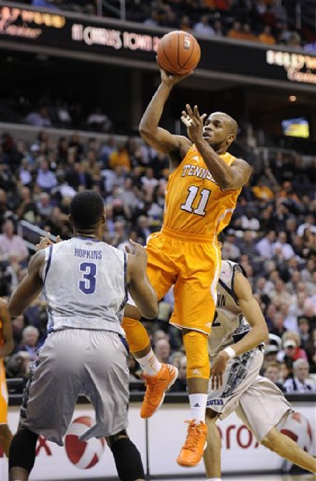 Tennessee guard Trae Golden (11) goes to the basket against Georgetown forward Mikael Hopkins (3) during the first half of an NCAA college basketball game, Friday, Nov. 30, 2012, in Washington.