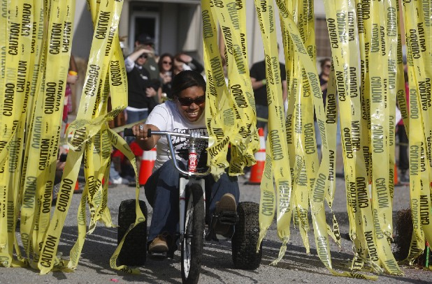 Kirsten Turner pedals her Big Wheel through a wall of ribbon during a race just off Main Street on Saturday afternoon during the MAINx24 festival. The 24-hour festival celebrated the art, music, and food of Chattanooga, and included local vendors, artists booths, performers, and activities for children and adults.