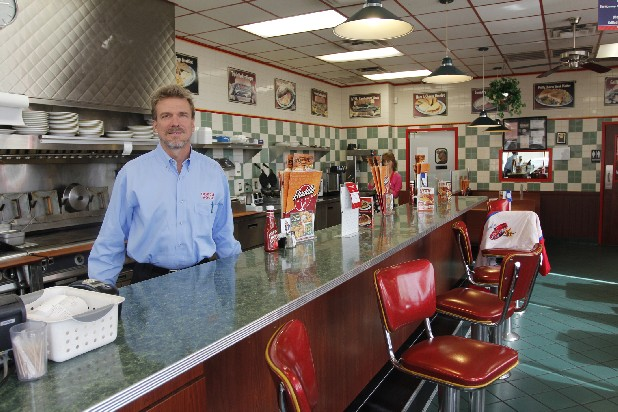 Gregg Hansen, Huddle House franchise owner, stands behind the counter for a portrait at the Huddle House restaurant on Hixson Pike in Hixson on Monday.