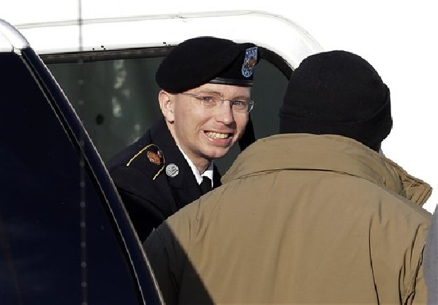 Army Pfc. Bradley Manning, center, steps out of a security vehicle as he is escorted into a courthouse in Fort Meade, Md., for a pretrial hearing.