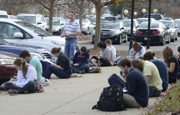 UTC professor David Aborn watches as students in his ecology class take final exams on the sidewalk Tuesday as several campus buildings were evacuated in response to a bomb threat.