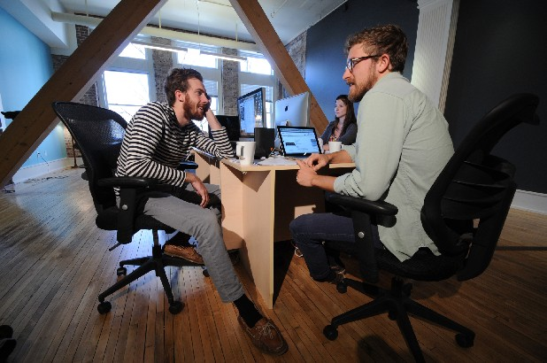 Fancy Rhino owners Drew Belz, left, and Isaiah Smallman talk business in their new digs in the old Loveman's building. Employee Helen Harrison is seen at her work station, back right.