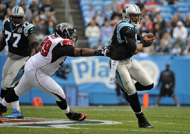 Carolina Panthers' Cam Newton (1) scrambles for a gain as Atlanta Falcons' Vance Walker (99) chases during the first half of an NFL  game in Charlotte, N.C., Sunday, Dec. 9, 2012.