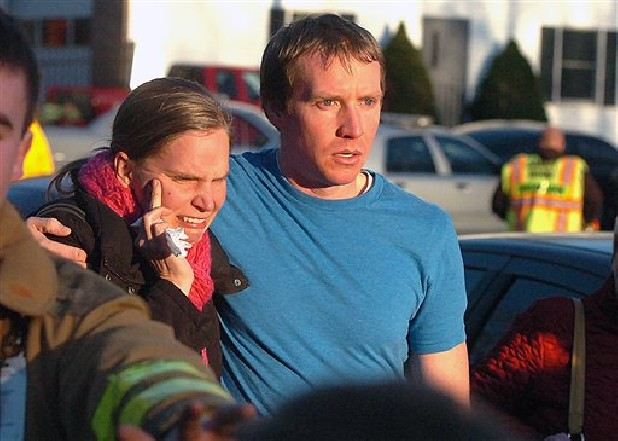 People leave the Sandy Hook Volunteer Fire House in tears after a shooting at the Sandy Hook Elementary School, Friday morning in Newtown, Conn.