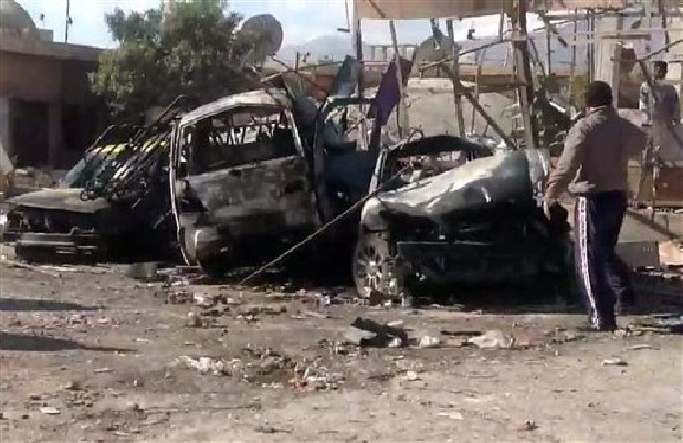 Syrian citizens gather next to cars that were destroyed by a car bomb in Qatana, 15 miles southwest of Damascus.