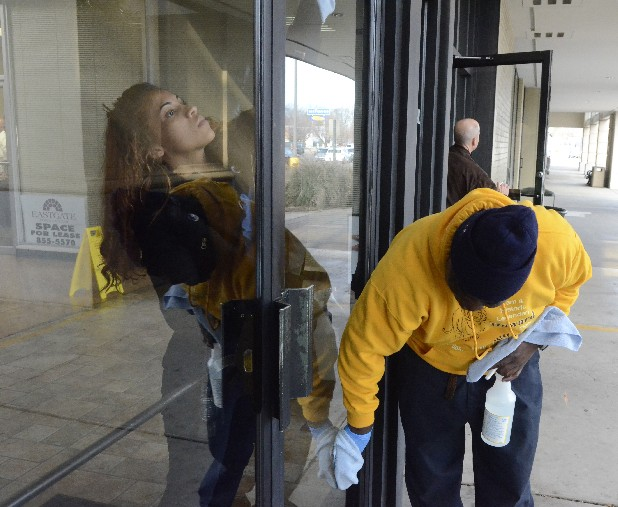 Marie White, left, and Isaac Harris wash windows Wednesday at the Eastgate Town Center.