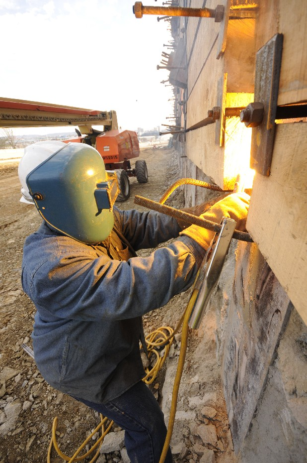 Malik January welds a shebolt bracket to the massive Highway 27 wall.