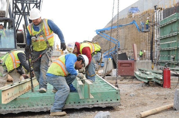 Workers prepare a concrete form for the construction of a retention wall along Highway 27 just north of downtown.