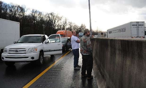 Barry Fisher, left, and Mike Mefford wait for traffic to resume on Interstate 24 East Thursday afternoon. A wreck caused a gridlock on the highway that lasted for about two hours.