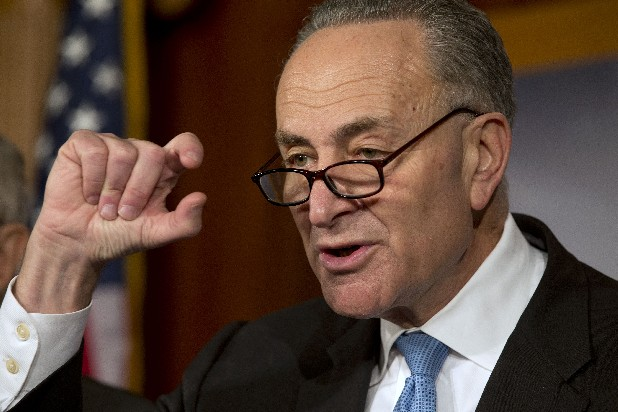 Sen. Charles Schumer, D-NY, gestures to show how close he says the speaker and the president are to a deal on the fiscal cliff, during a news conference at the U.S. Capitol in Washington on Thursday.