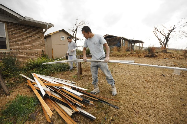 "Hugo Cortez, left, and Gustavo Garcia and  work to rebuild a house at 7401 Davis Mill Circle. ""The residents have been out of their house and in a motel for more than 6 months,"" Cortez said."