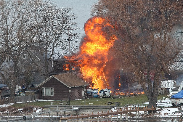 A house burns Monday, Dec. 24, 2012 in Webster, New York. A former convict set a house and car ablaze in his lakeside New York state neighborhood to lure firefighters then opened fire on them, killing two and engaging police in a shootout before killing himself while several homes burned. Authorities used an armored vehicle to evacuate the area. (AP Photo/Democrat & Chronicle, Jamie Germano)