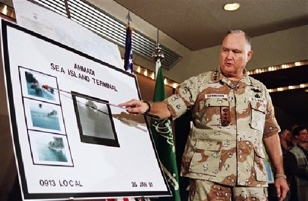 U.S. Army Gen. Norman Schwarzkopf points to row of photos of Kuwait's Ahmadi Sea Island Terminal on fire after Jan. 27, 1991, a U.S. attack on the facility. Schwarzkopf died Thursday in Tampa, Fla. He was 78.