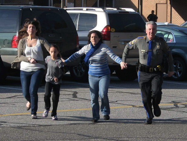 A police officer leads two women and a child away from the shooting scene at Sandy Hook Elementary School in Newtown, Conn., on Dec. 14.