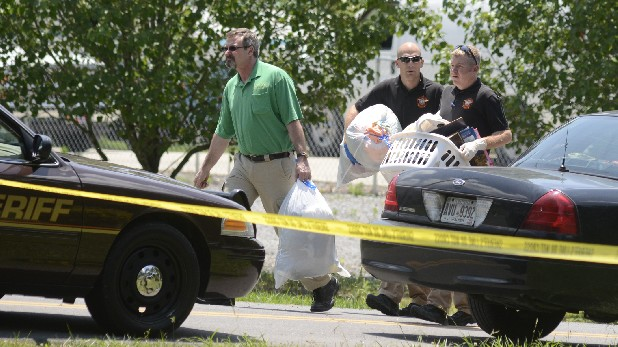 Investigators help a man carry items from the scene of the May 2012 slayings of Donald Shedd and Jessica Neal in the Dawnville community in northern Whitfield County, Ga.