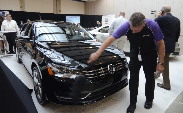 Larry Mutz dusts off a Volkswagen Passat at the Southern Automotive Conference Thursday at the Chattanooga Convention Center.