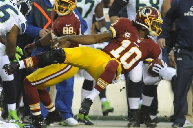 Washington Redskins quarterback Robert Griffin III flies through the air as he is knocked out of bounds Sunday during the first half of an NFL wild card playoff game against the Seattle Seahawks in Landover, Md.