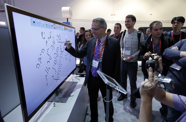 Moti Elmaliach, center, of Israel, writes on a display using Panasonic's electronic touch pen at the Panasonic booth at the International Consumer Electronics Show in Las Vegas.