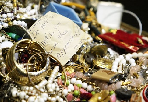 Costume jewelry is among the mass of seized stolen goods police displayed during a news conference in Hudson Falls, N.Y. Few clues exist pointing to the owners of the roughly 30,000 items discovered after 39-year-old burglary suspect John Suddard's recent arrest. So police are taking the novel step of displaying the items at the local high school Wednesday.
